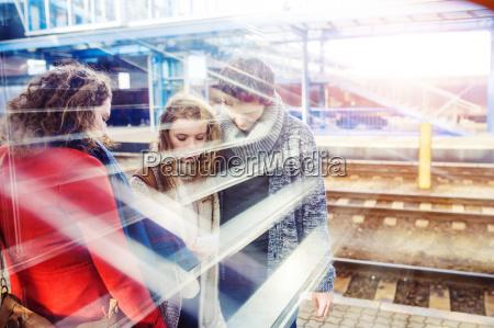 three friends on station platform
