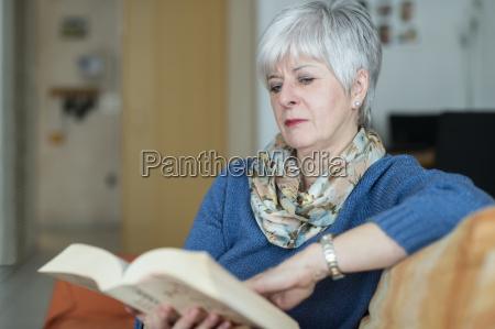 eine seniorin sitzt am fenster auf