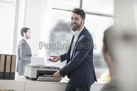 homem de sorriso no escritorio usando