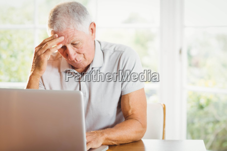 worried senior man using laptop