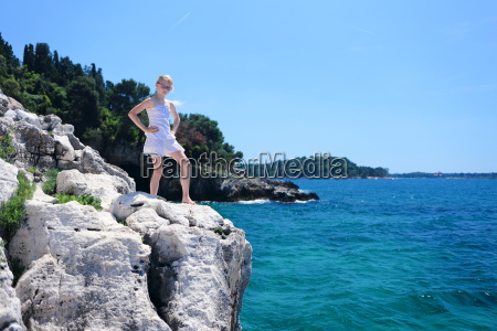 girl stands on sea cliff