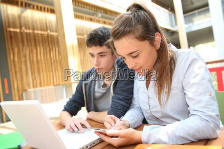 adolescentes que trabalham no portatil no