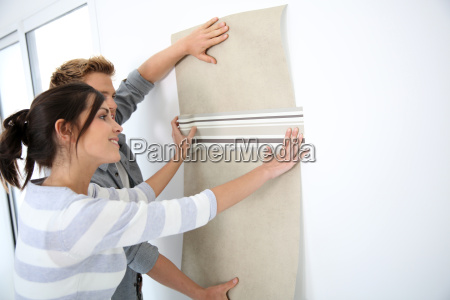 young couple choosing wallpaper for new