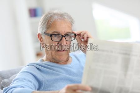 homem senior no jornal home da