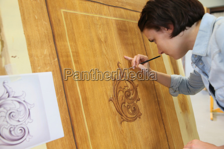 young woman creating trompe loeil art
