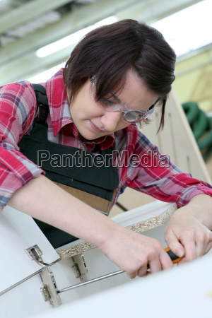 young woman carpenter assembling furniture