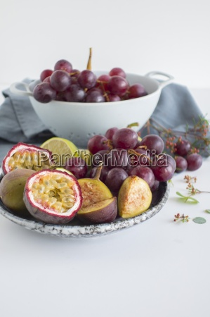a fruit bowl with grapes figs