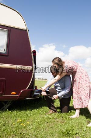 couple working on trailer in field