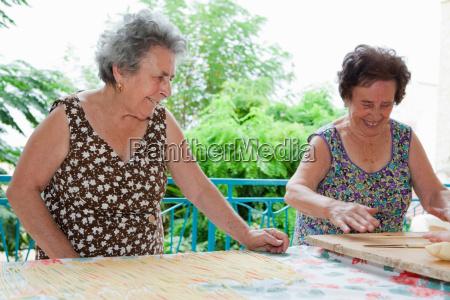 older women making pasta together