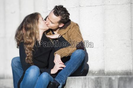 pares romanticos que beijam enquanto sentando