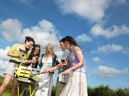 group of young people around barbecue
