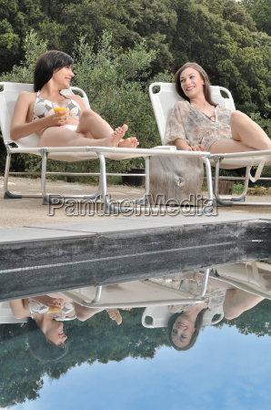 two women relaxing by the swimming