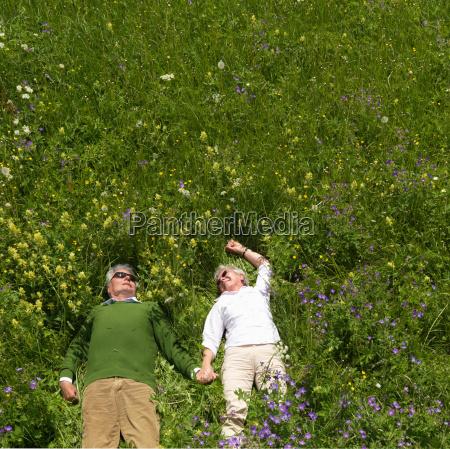 senior couple lying in field of
