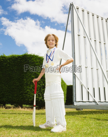 boy with cricket bat and medals