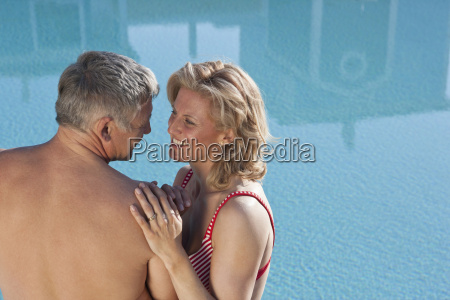 mature couple embracing by pool