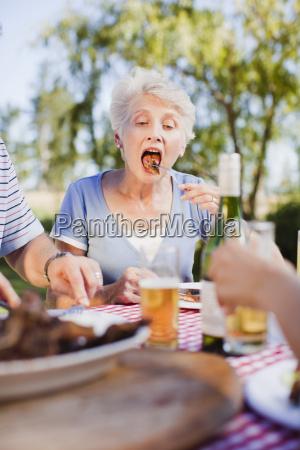 older woman eating at picnic table
