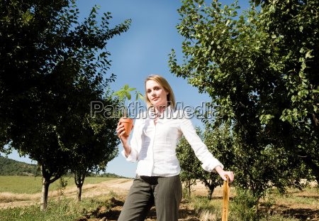 woman leaning on spade holding plant