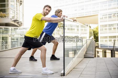 dois homens inclinando se e esticando