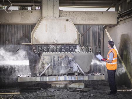 trabalhador de pedreira inspecionar serra de