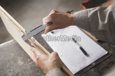 carpinteiro medindo prancha de madeira com