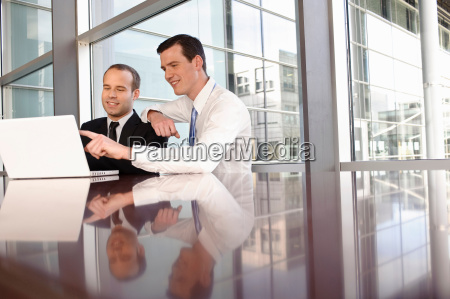 two young business men using laptop