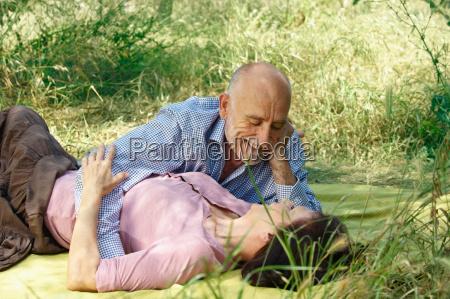 older couple embracing on picnic blanket