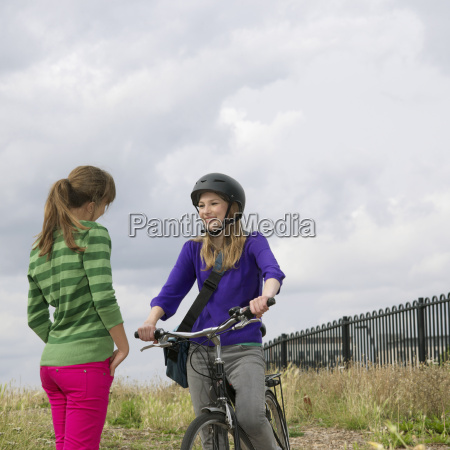 2 young women with bicycle chatting