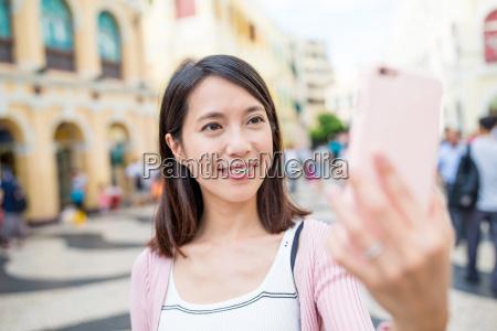 mulher que usa o telefone movel