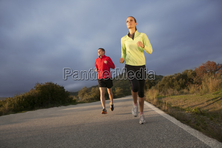 young couple jogging in rural setting