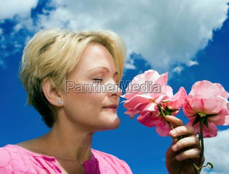 women smelling roses