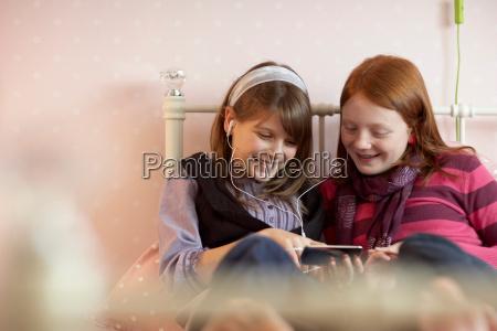 teenage girls sharing music player