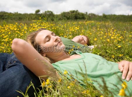 couple sleeping in meadow