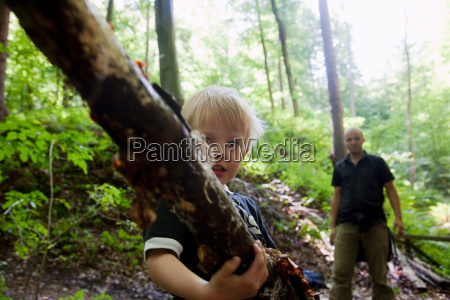 boy carrying a limb in a