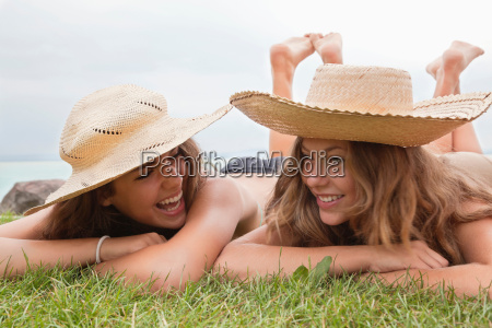 women in straw hats laughing together