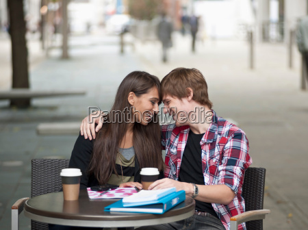 couple seated at cafe table embracing