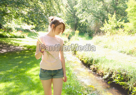 girl picking flowers by river