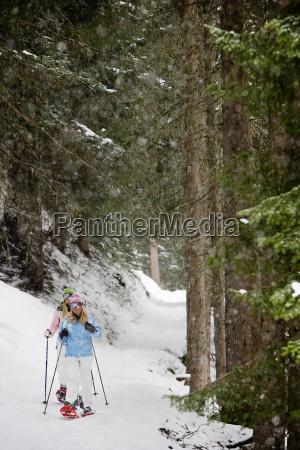 two blonde women walking in snow