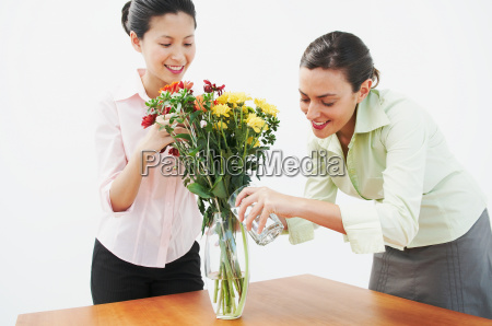 two woman watering flowers