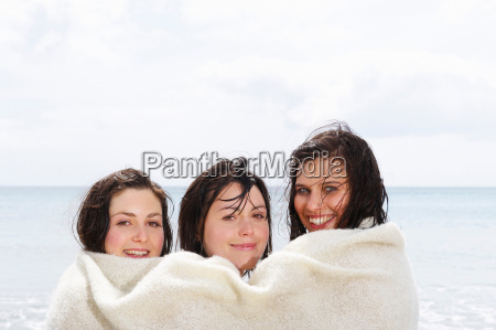 three girls sharing a blanket