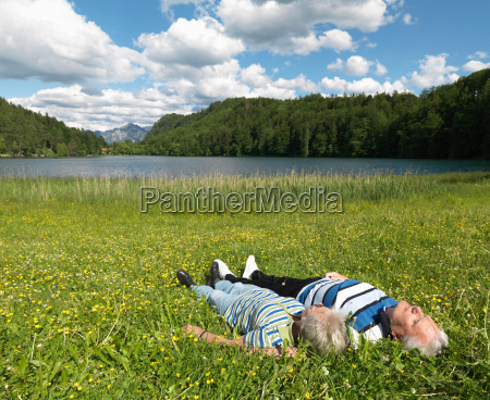 senior couple lying in field by