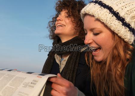women holding newspaper laughing