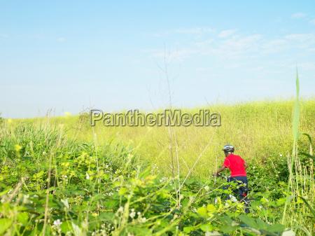 boy biking in field of flowers