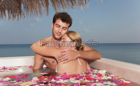 couple embracing in pool with petals
