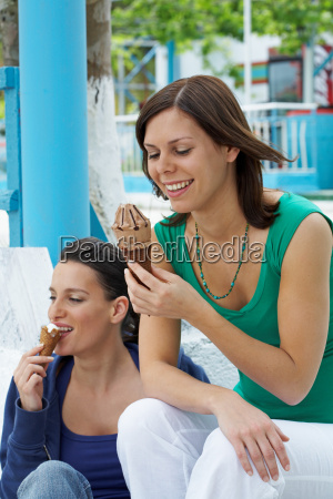 two smiling women sitting on steps