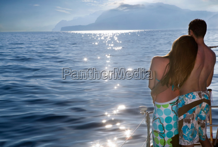 couple on sailboat at sunset