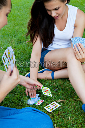 young women playing card game