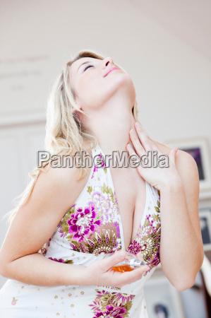 woman appreciatively applying perfume
