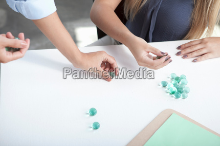 women playing with glass beads