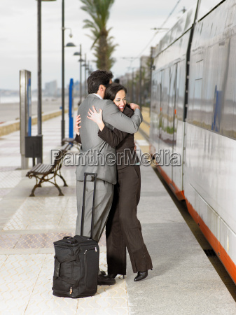 couple in suits embracing at tram
