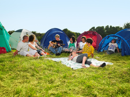 group sitting outside tents